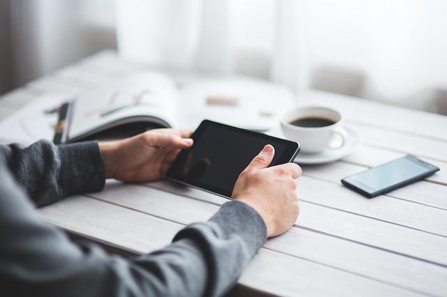 Mann am Tisch mit Pad in den Händen, Handy, Katalog und Tasse Kaffee auf dem Tisch
