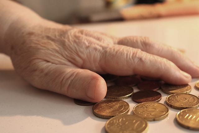 Hand einer alten Frau über einer Anzahl 20- und 50 Cent-Münzen